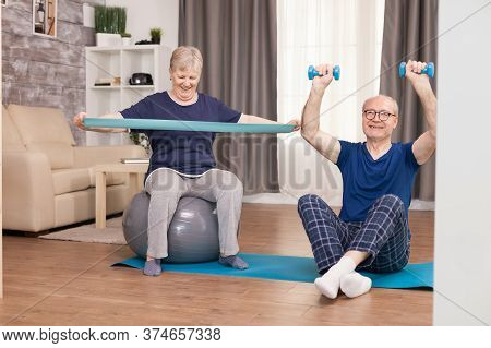 Senior Couple Exercising At Home Toning Their Arms. Old Person Healthy Lifestyle Exercise At Home, W