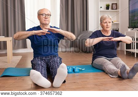 Senior Couple Stretching Their Bodies On Yoga Mat In Living Room. Old Person Healthy Lifestyle Exerc