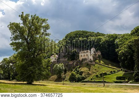 Gothic Building Of The Monastery, Built In A Mountain, Surrouded By Trees. Cloudy Sky In The Spring.