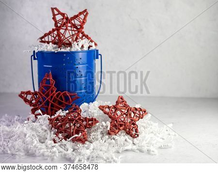 Red Wooden Stars And A Blue Metal Bucket Sitting On A Bed Of White Paper Shreds For The 4th Of July,