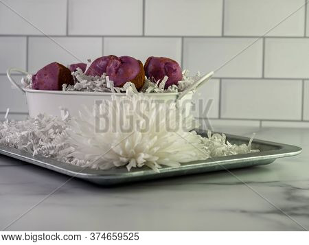 Purple Cinnamon Roll Cake Balls Piled In A White Bucket Filled With White Paper Shreds, Sitting On A