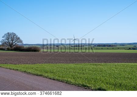 A Lonely Wind Power Plant Stands In The Middle Of The Farmlands In Skåne (scania) In Southern Sweden