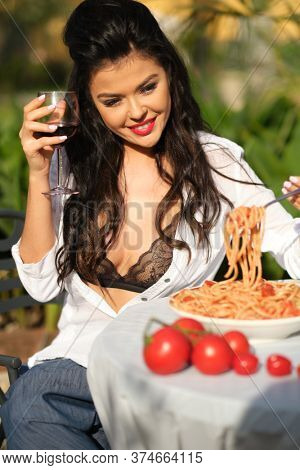 Healthy organic food, italy. Chef woman with red lips eat pasta. Hunger, appetite, recipe. Woman eating pasta in italian garden . Italian macaroni or spaghetti for dinner, cook.