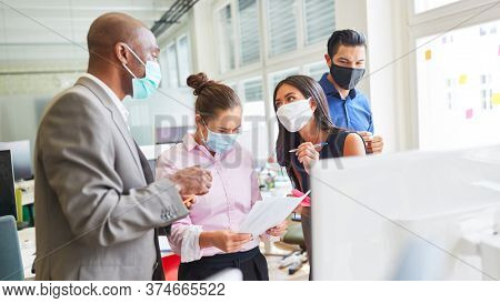 Business team with face mask for Covid-19 in a project meeting in the internet agency