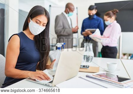 Business woman wearing face mask disinfect at work in the office because of Covid-19 and corona virus