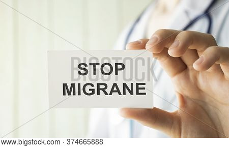 Doctor Holding A Card With Stop Migraine, Medical Concept
