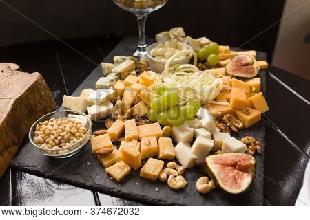 Cheese Assorted Or Cheeseboard. Gourmet Cheeses With Fig, Green Grapes And Nuts On Black Wooden Plan