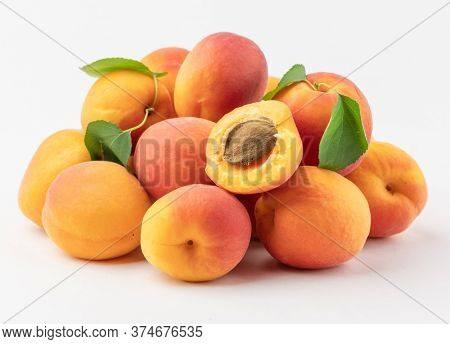 Heap of ripe apricot on a white background, seasonal yellow fruit, homemade apricot with leaves