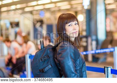 Woman Solo Travel. Portrait Of A Middle Aged Female Traveller Standing With Backpack In Airport.