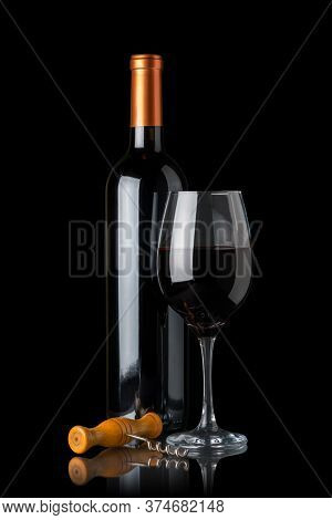 Bottle Of Red Wine Next To A Glass And A Corkscrew Isolated On Black Background