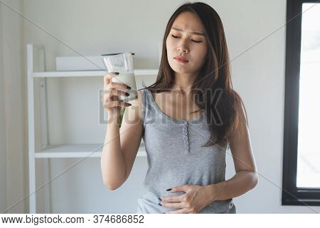 Lactose Intolerance Concept. Woman Holding A Glass Of Milk And Having A Stomachache.