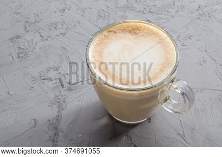 Transparent Cup Of Coffee With Latte Art On Concrete Table