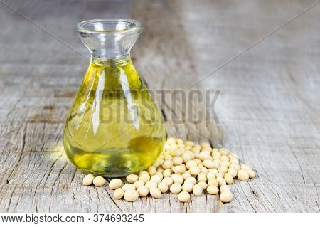Soybean Oil In Glass Jar And Soybean On The Woonden Background.