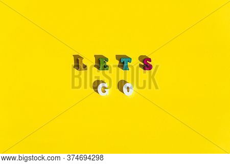 Flatlay Of Wood Multicolored Letters Is Inscription Of Lets Go With Shadows On Bright Plain Yellow B