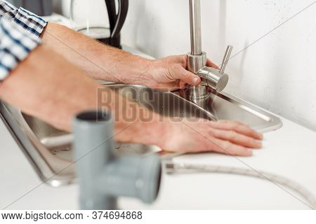 Focus Of Plumber Fixing Kitchen Faucet Near Pipes On Worktop