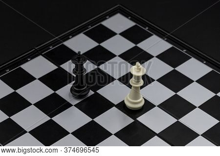 Black And White King On Chessboard. Victorious And Defeated King Figure. Chess Figurine Order. Check