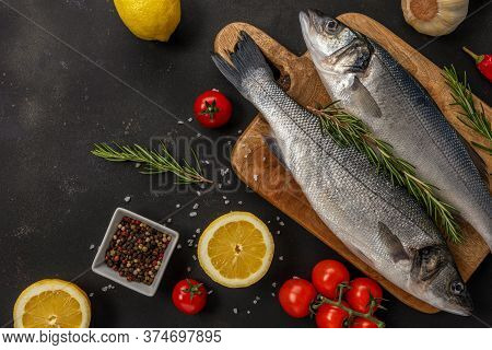 Two Fresh Seabass Fishes With Rosemary And Vegetables On Black Table. Seafood Concept.
