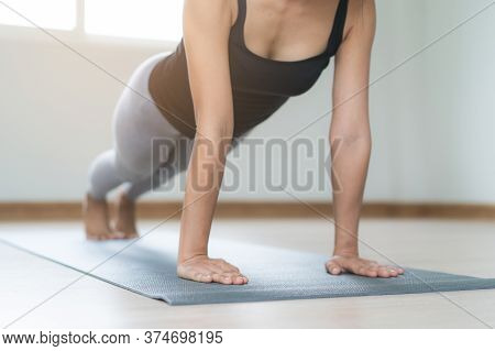 Woman Exercising Core Body At Home By Doing Plank Pose On The Yoga Mat.