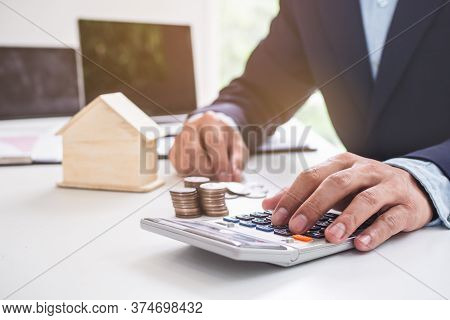 Businessman Investing In Real Estate Calculating Income And Analysing Mortgage Asset.