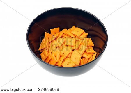 Black Ceramic Bowl filled with Cheese Flavored Crackers. Cheese Crackers in a bowl. Isolated on white. Room for text. People enjoy crackers world wide.