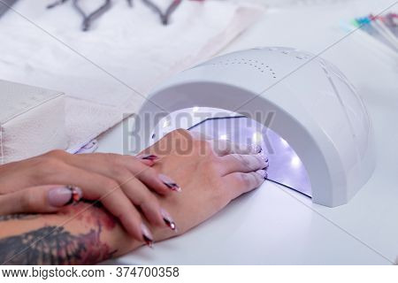 Womens Manicured Hands With A New Manicure While Drying The Varnish Gel In An Ultraviolet Led Lamp