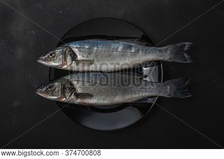 Two Fresh Seabass Fishes On A Black Plate. Seafood Concept.