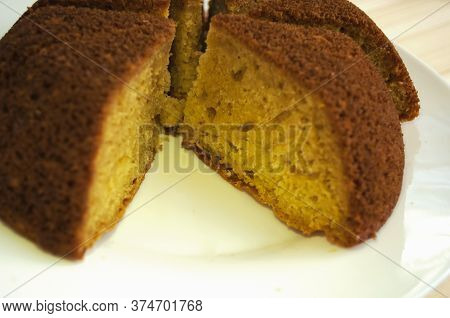 Sliced, Divided Sponge Pie Into Portions On A White Background Close Up. One Piece Is Taken Away