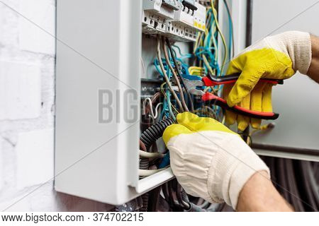 View Of Workman In Gloves Holding Pliers While Fixing Electrical Distribution Box