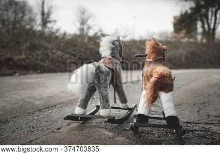 Abandoned Rocking Horses On The Road. Concept Of Abandonment, Loneliness, The End Of Childhood.