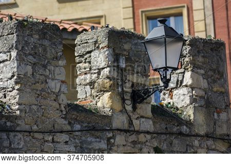 Photo Of A Stone Wall With (sun And Shadow), Streetlight And Sunlight.