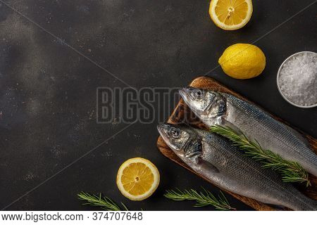 Two Fresh Seabass Fishes With Rosemary And Lemon On Black Table. Seafood Concept.