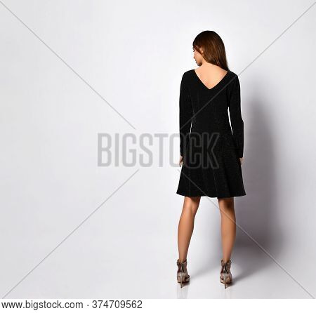 Rear View Of A Beautiful Young Female In A Glamour Black Minidress With A V-shaped Neckline On A Bac