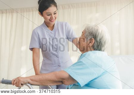 Cheerful Young Nurse In Homecare Helping Senior Patient Use Walker To Recovery From Hip Injury.
