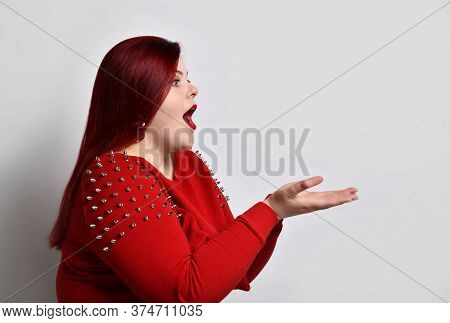 Fatty Redhead Model In Red Spiked Blouse And Earrings. She Is Acting Like Holding Something, Looking