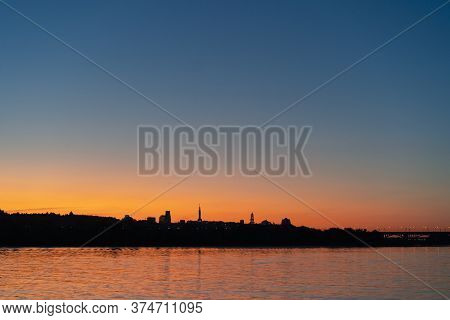 Sunset Over Dnipro River. View On Right Bank Of Dnieper. Cityscape With Silhouettes Of Motherland Fa