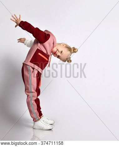 Cute Blonde Schoolgirl In Pink And Red Jym Suit Leaning Head Forward Taking Arms Back. Sports Fashio