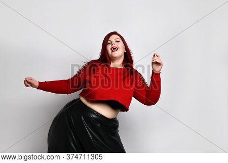 Obese Ginger Lady In Red Spiked Top, Black Bra And Leather Skirt, Earrings. She Is Dancing And Singi