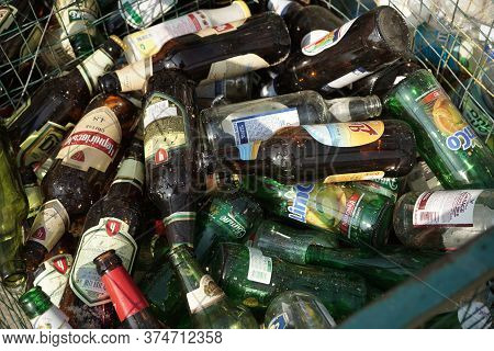 Glass Bottles From Beer And Lemonade In A Trash Can. Close Up Shot. Sorting And Recycling Garbage Co
