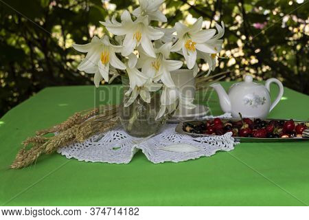 On The Table In The Summerhouse There Is A Bouquet Of White Lilies, A Tray With Ripe Berries, A Teap