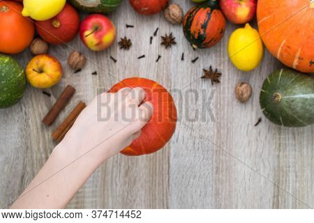 Female Hand Holds A Pumpkin Over The Autumn Background. Autumn Background Of Pumpkins And Fruits On