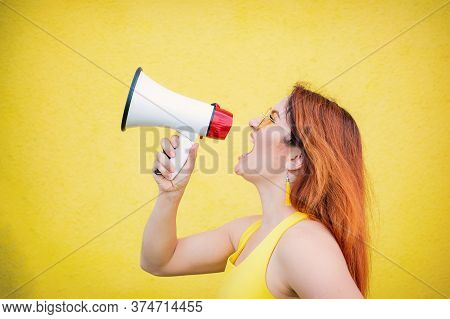 A Woman In A Dress With Glasses And Earrings Stands In Profile On A Yellow Background And Shouts In