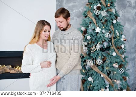 Young Couple Expecting Baby Near Christmas Tree. Pregnant Woman With Husband.