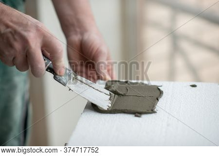 A man putsglue with putty knife on foam to stick it to the ceiling. Styrofoam, seiling mounting. A man glues foam. Ceiling insulation. Warming. Repair in the house. Male hands with tools. DIY repair