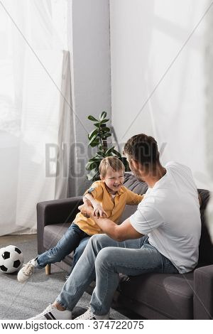 And Happy Son Jokingly Fighting On Sofa Near Soccer Ball