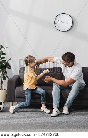 Happy Father And Son Having Fun While Jokingly Fighting On Sofa At