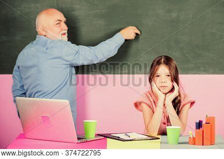 Bored Pupil. Little Girl With Man Tutor Study On Notebook. Mature Teacher Help School Girl. School L