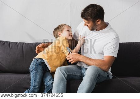 Father And Son Having Fun While Jokingly Fighting On Sofa At Home