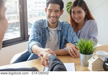 New House / Home Moving And Relocation Concept. Happy Asian Couple Shaking Hands With Real Estate Co