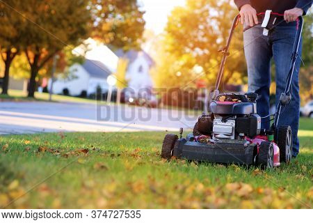 Mowing The Grass With A Lawn Mower In Sunny Autumn. Gardener Cuts The Lawn In The Garden