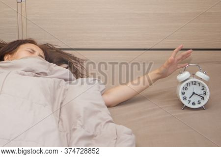 Woman Looking For Alarm Clock In The Morning Trying To Shut Off Snooze.